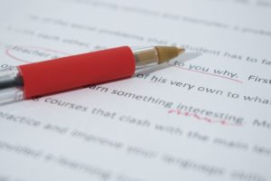 Red correction pen lying on an edited text